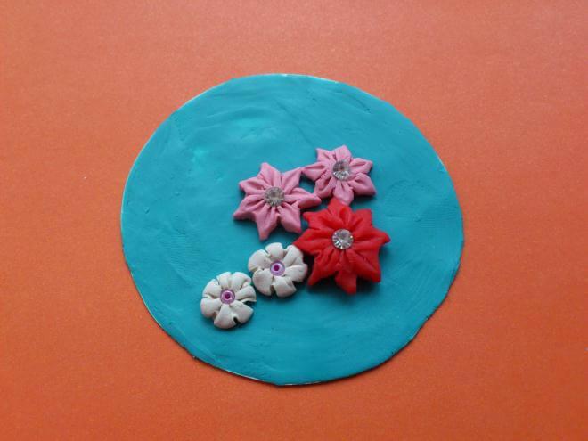 В центр каждого цветочка приклейте камушек